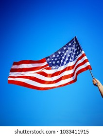 American flag holding in woman hand on the blue sky background