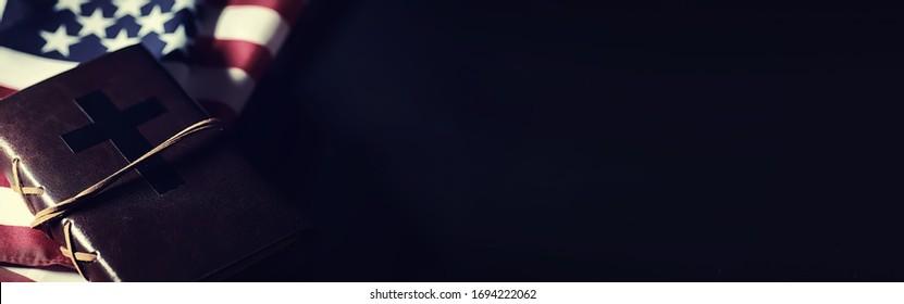 Amerikanische Flagge und heiliges Bibelbuch auf Spiegelhintergrund. Symbol der Vereinigten Staaten und Religion. Bibel und gestreifte Flagge auf schwarzem Hintergrund.
