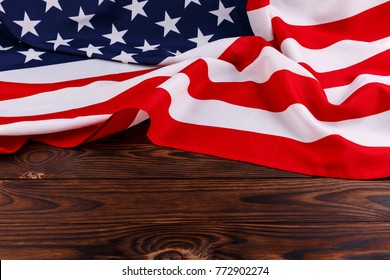 American flag lies on top of a wooden background close-up