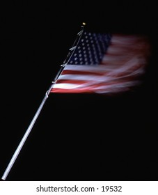American flag lit at night a beacon in the darkness.