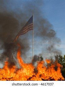 American flag obscured by burning fires in foreground
