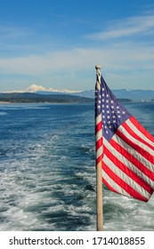 American flag on a boat against the sea and Mt. (mountain) Baker