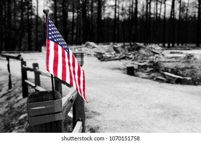 American flag on the end of a fence in front of fire-destroyed structures.