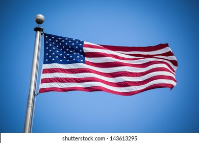 American flag on a flagpole blowing in the wind against a blue sky
