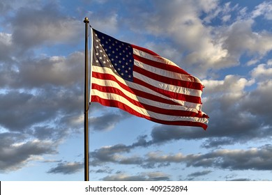 American flag on flagpole waving in the wind against clouds, blue sky and the moon