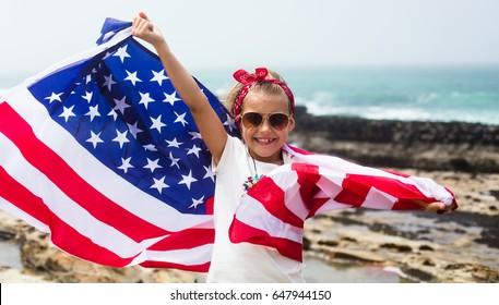 American flag on Independence Day, July 4th: little smiling  patriotic girl with long blond hair, red head  bandana and sunglasses holding an American flag waving in the wind on the ocean beach