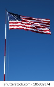 American flag on a pole blowing in the breeze with blue sky in the background.