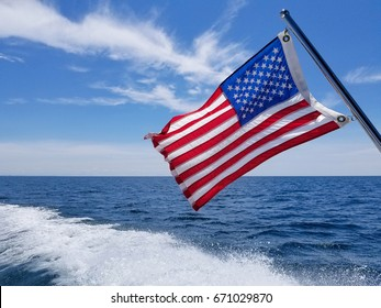 American flag on pole with boat wake on Lake Michigan