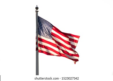 American flag on pole flowing in the wind. Isolated on white background, close-up