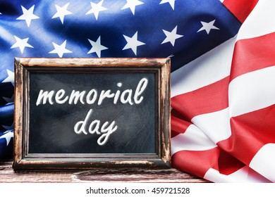 "American flag on a wooden table with the inscription ""memorial day"""