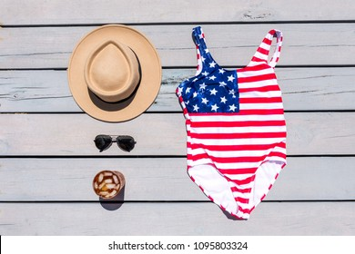 American Flag One Piece Swimsuit Bathing Suit on Dock Pier Hat Sunglasses Iced Tea July Fourth Memorial Day Labor Day Patriotic Summer Relax Vacation Red White Blue Flatlay from Above