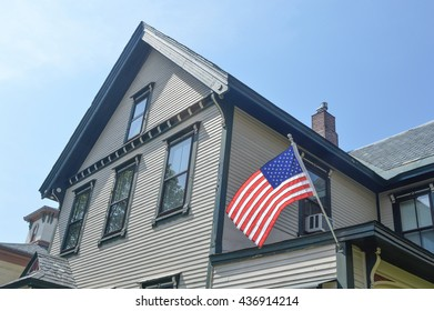 An American flag out in the spring time on the old house