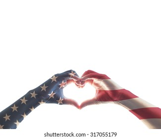 American flag pattern on people hands in heart love shape isolated on white background