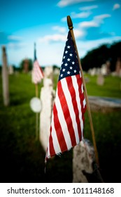 American flag placed on gravestone in graveyard for Fourth of July holiday, processed in moody style