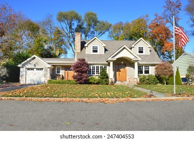 American flag pole beautiful suburban cape cod style home autumn clear blue sky day residential neighborhood USA