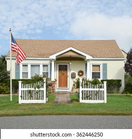 American Flag pole Beautiful Suburban Bungalow Cottage style home with white picket fence flowers residential neighborhood Blue Sky Clouds USA