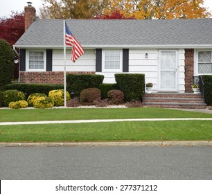 American Flag pole Close up of Ranch style Home Autumn Day Residential Neighborhood USA