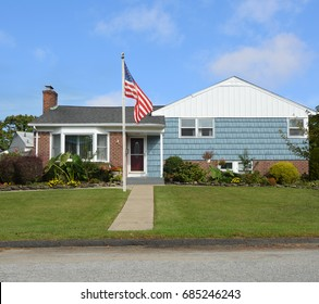 American flag pole front yard lawn of Suburban home ranch style house bay window USA blue sky clouds