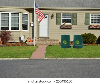 American flag pole Green recycle, reuse, reduce, trash container closeup view Suburban home landscaped lawn sunny residential neighborhood autumn day USA