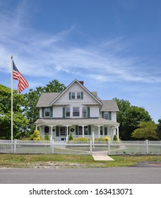 American Flag Pole Large Suburban Home with White Picket Fence Sunny Blue Sky Clouds USA Residential Neighborhood