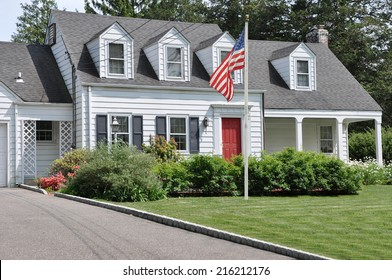 American Flag Pole on front yard lawn of Suburban Cape Cod Colonial Style Home Sunny Residential Neighborhood USA