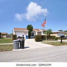 American Flag pole on front yard lawn of suburban ranch style home residential neighborhood sunny blue sky clouds USA