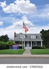 American Flag Pole Real Estate For Sale Welcome Open House Sign on front yard lawn of Suburban House in Residential Neighborhood Blue Sky Clouds USA