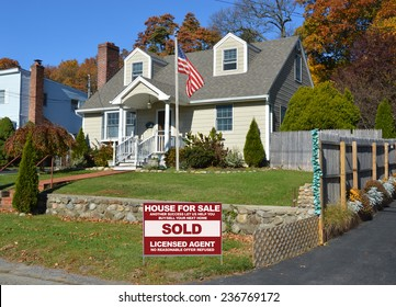 American flag pole Real Estate sold (another success let us help you buy sell your next home) sign Suburban home autumn day residential neighborhood blue sky USA