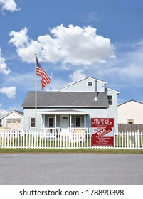 American Flag Pole Sold real estate sign (another success let us help you buy sell your next home) white picket fence Suburban Home Residential neighborhood USA Blue Sky Clouds