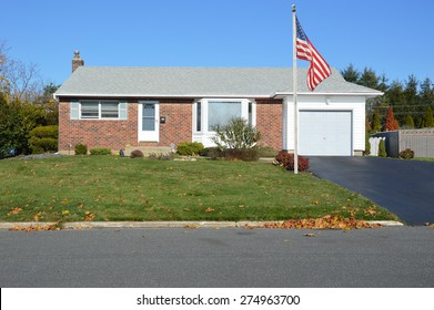 American flag pole Suburban brownstone brick ranch style home sunny clear blue sky residential neighborhood USA