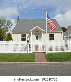 American Flag Pole Suburban Bungalow style home White Picket Fence blue sky clouds Day Residential Neighborhood USA