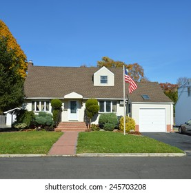 American flag pole Suburban cape cod style home sunny clear blue sky autumn day residential neighborhood USA