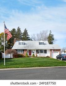 American flag pole suburban cape cod style home autumn blue sky clouds day residential neighborhood USA