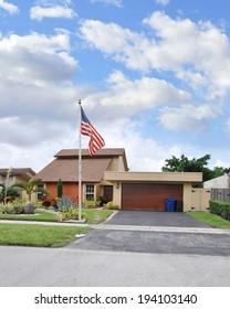 American Flag pole Suburban home Residential Neighborhood USA Blue sky clouds