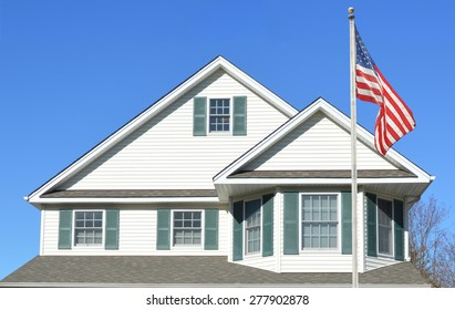American Flag pole Suburban Home Roof Windows Sunny clear blue sky day residential neighborhood USA
