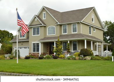 American flag pole Suburban McMansion style home overcast cloudy day residential neighborhood USA