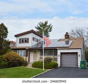 American flag pole Suburban Ranch style home with solar panel on roof residential neighborhood USA blue sky clouds