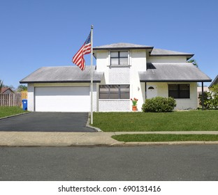 American Flag pole Suburban White split level ranch with double wide garage blacktop driveway blue sky USA