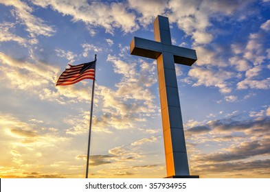 American flag and religious cross at sunset