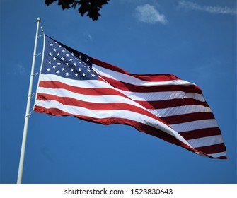 An American Flag ripples in the hot breeze against a bright, blue sky.