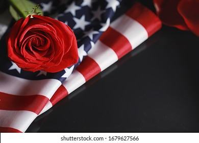 American flag and rose flower on table. Symbol of the United States of America and red petals. Patriotism and memory.