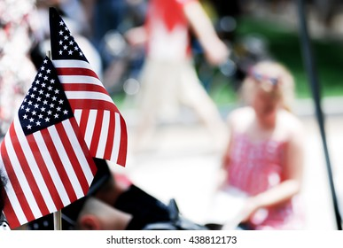 American flag show by people on 4th of july parade, god bless America, American flags attached background of a girl and peoples in a Fourth of July parade.