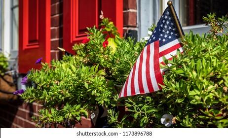 An American flag sits in a flower planter near a window in Philadelphia, PA.