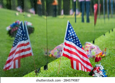 American Flag sits next to a traveling Vietnam memorial wall with the flags reflection.