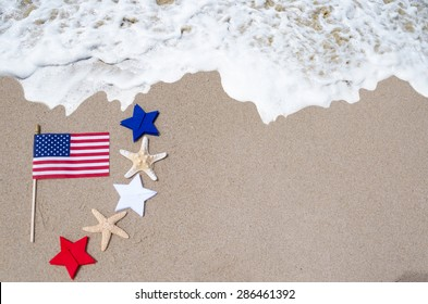 American flag with starfishes, white, blue and red stars on the sandy beach - USA holidays concept