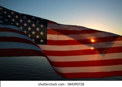 American Flag Stars and Stripes Flapping in the Breeze with Yellow Orange Setting Sun Half-Tansparent Gleaming Through, Water Below and Blue Sky Above, Quiet Waters Park Lake, Deerfield Beach, Florida