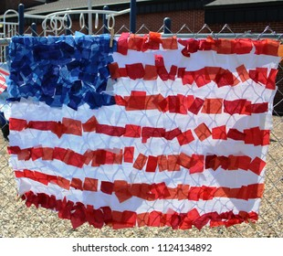 American Flag Stars and Stripes made of crepe paper streamer bits hang on fence at playground. Red white and blue.
