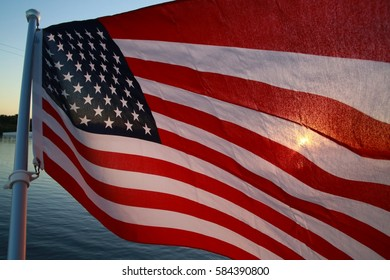 American Flag Stars and Stripes on Metal Pole Flapping in the Breeze with Yellow Orange Setting Sun Half-Tansparent Gleaming Through on Quiet Waters Park Lake, Deerfield Beach, Florida