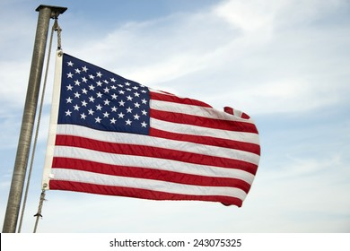 The American flag, The Stars and Stripes; Red, White and Blue; Old Glory; The Star-Spangled Banner. Flying in the wind with a blue cloudy sky in the background.