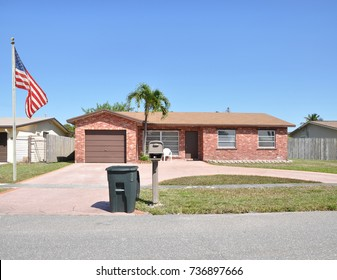 American flag Suburban Brick Ranch style home with trash container next to mailbox blue sky USA